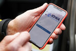 FILE - In this Nov. 15, 2019, file photo, a precinct captain from Des Moines, Iowa, holds his iPhone showing the Iowa Democratic Party's caucus-reporting app. The botched Iowa caucuses may have been a cautionary tale on the perils of relying on previously unused technology for a grand civic event such as an election or the census. (AP Photo/Charlie Neibergall, File)