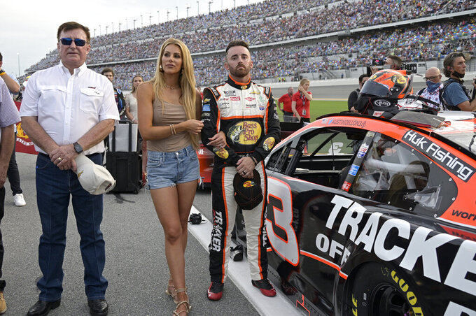 Austin Dillon stands next to his vehicle with his wife Whitney Dillon and car owner Richard Childress, left, on pit road before a NASCAR Cup Series auto race at Daytona International Speedway, Saturday, Aug. 28, 2021, in Daytona Beach, Fla. (AP Photo/Phelan M. Ebenhack)