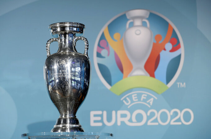 FILE - In this Thursday, Oct. 27, 2016 file photo, the Euro soccer championships trophy is seen in front of the logo during the presentation of Munich's logo as one of the host cities of the Euro 2020 European soccer championships in Munich, Germany. With 100 days to go, UEFA is pushing ahead with staging the European Championship across the continent. All 12 cities, however, might no longer make the cut. Bilbao, Dublin and Glasgow risk being dropped over the lack of guarantees about the number of fans that could be allowed into stadiums by June 2021. (AP Photo/Matthias Schrader, File)