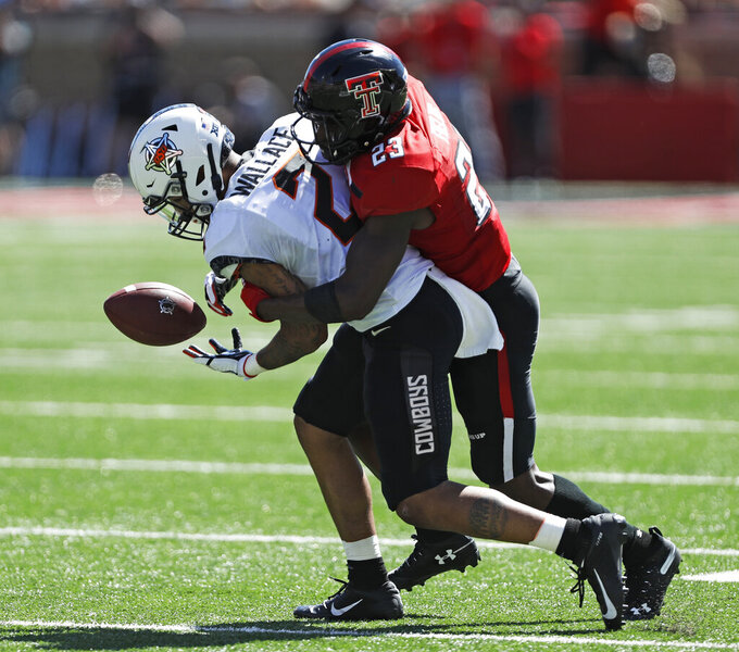 Texas Tech's Damarcus Fields (23) tackles Oklahoma State's Tylan Wallace (2) to break up a pass during the second half of an NCAA college football game Saturday, Oct. 5, 2019, in Lubbock, Texas. (AP Photo/Brad Tollefson)