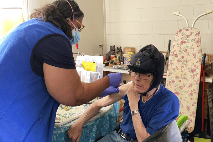 Alameda County nurse Patricia Calloway administers a COVID-19 vaccine to William Brainerd inside his studio apartment in San Leandro, Calif., May 6, 2021. Brainerd, who says he cannot wear a mask because of respiratory issues, has not left his apartment complex since the pandemic began.   (AP Photo/Terry Chea)