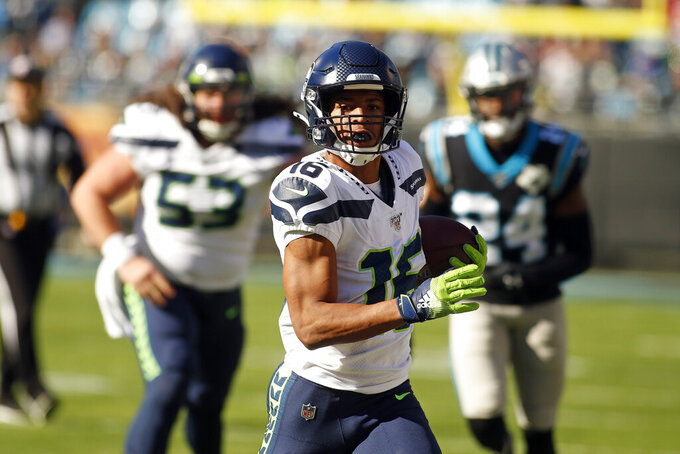 Seattle Seahawks wide receiver Tyler Lockett (16) runs the ball against the Carolina Panthers during the first half of and NFL football game in Charlotte, N.C., Sunday, Dec. 15, 2019. (AP Photo/Brian Blanco)