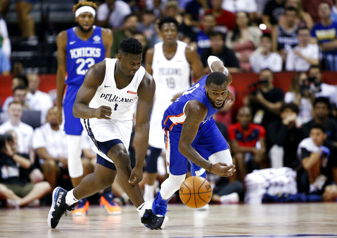 New Orleans Pelicans' Zion Williamson, left, and New York Knicks' Kadeem Allen chase the ball during an NBA summer league basketball game Friday, July 5, 2019, in Las Vegas. (AP Photo/Steve Marcus)