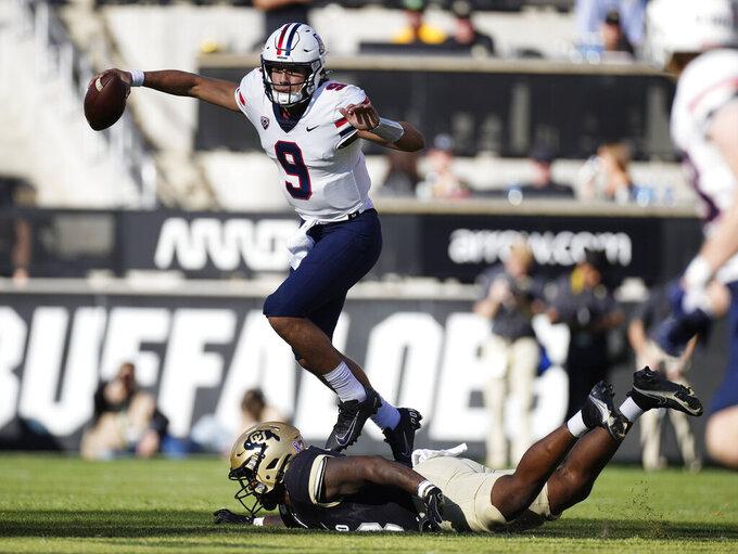Arizona quarterback Gunner Cruz, top, jumps over Colorado defensive lineman Justin Jackson in the second half of an NCAA college football game Saturday, Oct. 16, 2021, in Boulder, Colo. (AP Photo/David Zalubowski)