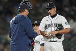 Seattle Mariners starting pitcher Yusei Kikuchi is pulled from the baseball game against the Kansas City Royals by manager Scott Servais, left, during the sixth inning Thursday, Aug. 26, 2021, in Seattle. (AP Photo/Ted S. Warren)
