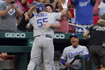 Los Angeles Dodgers' Albert Pujols (55) gets a hug from teammate Max Muncy after hitting a solo home run as Dodgers manager Dave Roberts, right, watches during the first inning of a baseball game against the St. Louis Cardinals Tuesday, Sept. 7, 2021, in St. Louis. (AP Photo/Jeff Roberson)