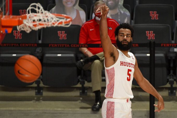 Houston guard Cameron Tyson watches his 3-point basket during the second half of an NCAA college basketball game against Lamar, Wednesday, Nov. 25, 2020, in Houston. (AP Photo/Eric Christian Smith)