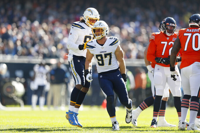 Los Angeles Chargers defensive end Joey Bosa (97) celebrates with teammate Isaac Rochell, left, after sacking Chicago Bears quarterback Mitchell Trubisky during the first half of an NFL football game, Sunday, Oct. 27, 2019, in Chicago. (AP Photo/Charlie Neibergall)