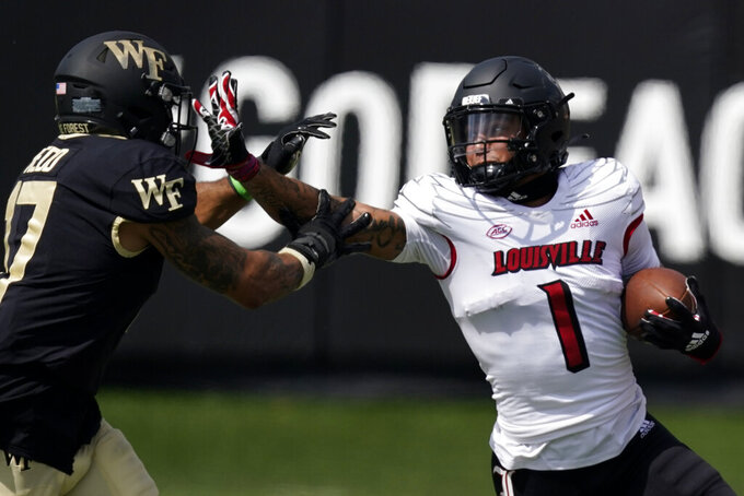 Louisville wide receiver Jordan Watkins runs past Wake Forest defensive back Traveon Redd during the first half of an NCAA college football game on Saturday, Oct. 2, 2021, in Winston-Salem, N.C. (AP Photo/Chris Carlson)