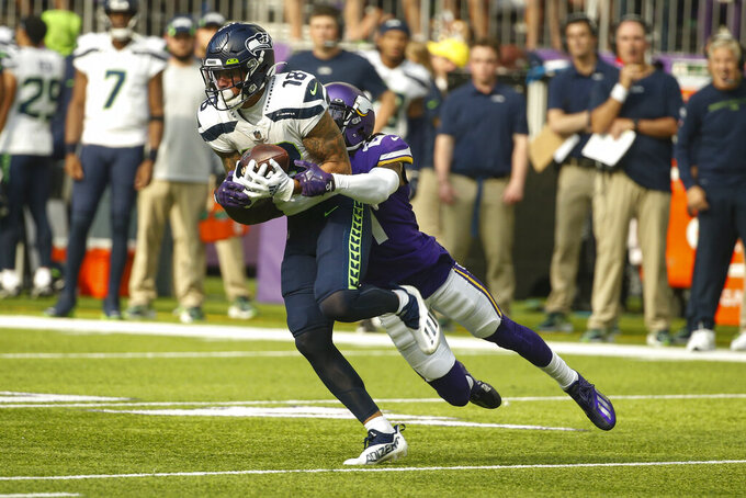 Seattle Seahawks wide receiver Freddie Swain (18) makes a catch in front of Minnesota Vikings defensive back Bashaud Breeland (21) in the first half of an NFL football game in Minneapolis, Sunday, Sept. 26, 2021. (AP Photo/Bruce Kluckhohn)