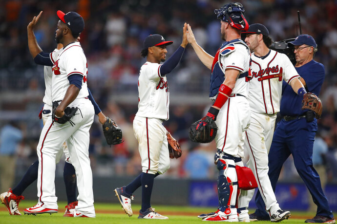 Atlanta Braves' Ozzie Albies, center, and teammates celebrate a 9-5 win over the Toronto Blue Jays in a baseball game Wednesday, July 11, 2018, in Atlanta. (AP Photo/Todd Kirkland)
