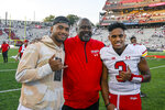 Maryland's head coach Mike Locksley, center, quarterback Taulia Tagovailoa, right, and his older brother Tua Tagovailoa celebrate a win against West Virginia in an NCAA college football game Saturday, Sept. 4, 2021 in College Park, Md. (Kevin Richardson/The Baltimore Sun via AP)