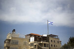 In this March 13, 2019 photo, an Israeli flag flies on a building in east Jerusalem's Mount of Olives. The Falic family, owners of the ubiquitous chain of Duty Free America shops, fund a generous, and sometimes controversial, philanthropic empire in Israel that stretches deep into the West Bank. The family supports many mainstream causes as well as far right causes considered extreme even in Israel. (AP Photo/Ariel Schalit)