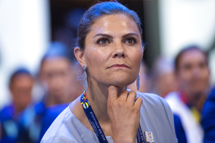 Member of the candidate for the Olympic Winter Games 2026 Stockholm-Are delegation, Crown Princess Victoria listens after International Olympic Committee (IOC) president Thomas Bach from Germany, right, announced that Milan-Cortina has won the bid to host the 2026 Winter Olympic Games, during the first day of the 134th Session of the International Olympic Committee (IOC), at the SwissTech Convention Centre, in Lausanne, Switzerland, Monday, June 24, 2019. Italy will host the 2026 Olympics in Milan and Cortina d'Ampezzo, taking the Winter Games to the Alpine country for the second time in 20 years. (Jean-Christophe Bott/Keystone via AP)