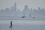 A man rides a powered surfboard on the bay with the San Francisco skyline in the background Saturday, Sept. 5, 2020, in Sausalito, Calif. California is sweltering under a dangerous Labor Day weekend heat wave that was expected to spread triple-digit temperatures over much of the state while throngs of people might spread the coronavirus by packing beaches and mountains for relief. (AP Photo/Eric Risberg)