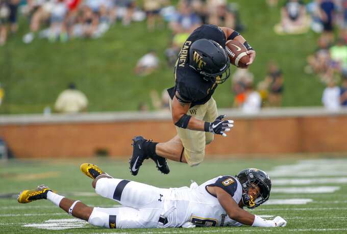 Wake Forest running back Cade Carney dives over Towson defensive back Jamal Gay in the second half of an NCAA college football game in Winston-Salem, N.C., Saturday, Sept. 8, 2018. (AP Photo/Nell Redmond)