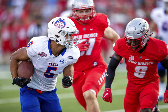Houston Baptist wide receiver Charles King (5) is chased by New Mexico safety Jerrick Reed (9) and defensive end Adam Gay during the first half of an NCAA college football game on Thursday, Sept. 2, 2021, in Albuquerque, N.M. (AP Photo/Andres Leighton)
