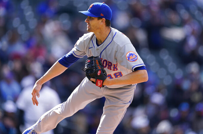 New York Mets starting pitcher Jacob deGrom watches a throw to Colorado Rockies' C.J. Cron during the fourth inning of the first baseball game game of a doubleheader Saturday, April 17, 2021, in Denver. (AP Photo/David Zalubowski)