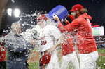 St. Louis Cardinals starting pitcher Miles Mikolas is doused by teammate Michael Wacha, right, while being interviewed by television reporter Jim Hayes, left, after throwing a complete game shutout against the Pittsburgh Pirates in a baseball game Monday, July 15, 2019, in St. Louis. (AP Photo/Jeff Roberson)