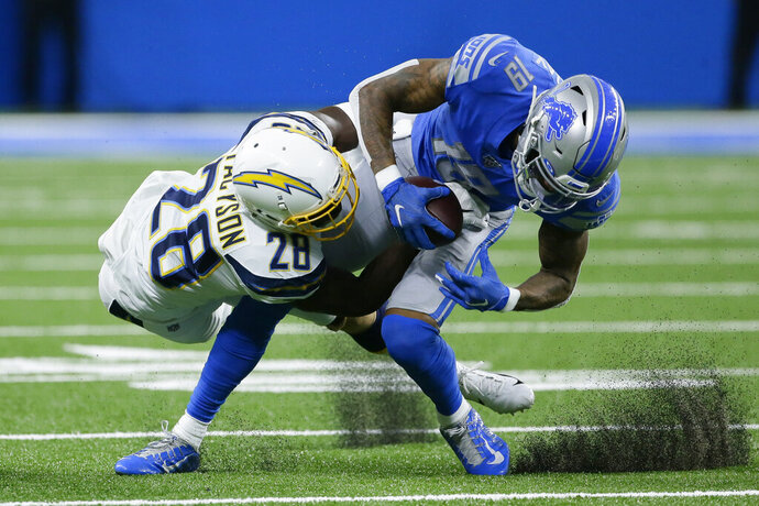 Los Angeles Chargers defensive back Brandon Facyson (28) brings Detroit Lions wide receiver Kenny Golladay (19) down after a reception in the first half of an NFL football game in Detroit, Sunday, Sept. 15, 2019. (AP Photo/Duane Burleson)