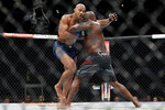 Ciryl Gane, left, and Derrick Lewis, right, compete during their interim heavyweight mixed martial arts title bout at UFC 265 on Saturday, Aug. 7, 2021, in Houston. (AP Photo/Michael Wyke)