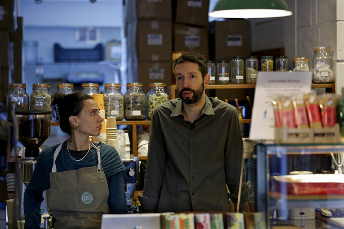 Paulina Filippou and Grigorios Vaitsas are interview by The Associated Press in their 'Isle of Olive' Natural Greek Products store and delicatessen, which can stay open for takeaway food and drink and online orders during England's second coronavirus lockdown, on Ada Street, off Broadway Market in Hackney, east London, Tuesday, Nov. 17, 2020. The Isle of Olive deli has survived the coronavirus even though the indoor cafe is closed and Christmas shopping events have been canceled. (AP Photo/Matt Dunham)