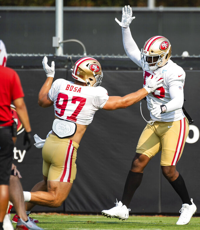 San Francisco 49ers defensive end Nick Bosa (97) gets a hand on defensive end Dee Ford (55) during drills at NFL football training camp Friday, Aug. 21, 2020, in Santa Clara, Calif. (Xavier Mascareñas/The Sacramento Bee via AP)