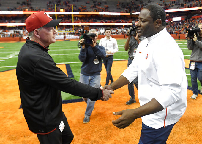 Louisville head coach Bobby Petrino, left, and Syracuse head coach Dino Babers shake hands after an NCAA college football game in Syracuse, N.Y., Friday, Nov. 9, 2018. (AP Photo/Adrian Kraus)