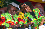 FILE - In this June, 2, 2017, file photo, Zimbabwe's President Robert Mugabe, left, and his wife Grace attend a youth rally in Marondera, Zimbabwe. Known as a strong-willed woman with political ambitions, Grace Mugabe rose from being one of the president's secretaries to become first lady. (AP Photo/Tsvangirayi Mukwazhi, File)