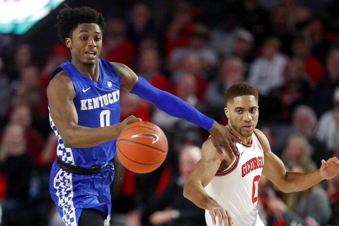 Kentucky guard Ashton Hagans (0) and Georgia guard Donnell Gresham Jr. (0) chase down a a loose ball in the first half of an NCAA college basketball game Tuesday, Jan. 7, 2020, in Athens, Ga. (AP Photo/John Bazemore)