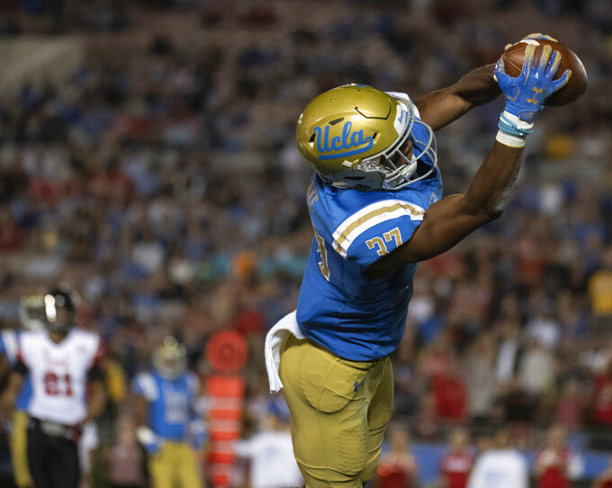 UCLA defensive back Quentin Lake intercepts a pass intended to Utah wide receiver Samson Nacua, not shown, during the first half of an NCAA college football game Friday, Oct. 26, 2018, in Pasadena, Calif. (AP Photo/Kyusung Gong)