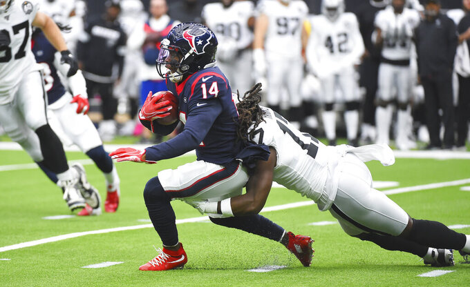 Houston Texans wide receiver DeAndre Carter (14) is hit by Oakland Raiders defender Dwayne Harris (17) after a catch during the first half of an NFL football game Sunday, Oct. 27, 2019, in Houston. (AP Photo/Eric Christian Smith)