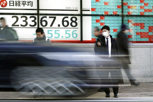 People walk past an electronic stock board showing Japan's Nikkei 225 index at a securities firm in Tokyo Tuesday, Feb. 18, 2020. Shares have fallen in Asia as the impact from the virus outbreak that began in China deepened, with Apple saying it would fail to meet its profit target and China moving to cancel major events including the Beijing auto show. (AP Photo/Eugene Hoshiko)