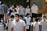 Students wearing face masks to protect against the new coronavirus leave school after finishing the first day of China's national college entrance examinations, known as the gaokao, in Beijing, Tuesday, July 7, 2020. China's college entrance exams began in Beijing on Tuesday after being delayed by a month due to the coronavirus outbreak. (AP Photo/Andy Wong)