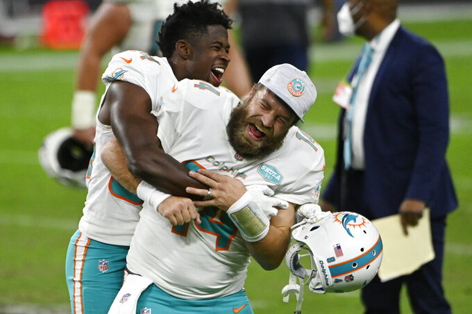 Miami Dolphins wide receiver Isaiah Ford, left, celebrates with quarterback Ryan Fitzpatrick after defeating the Las Vegas Raiders in an NFL football game, Saturday, Dec. 26, 2020, in Las Vegas. (AP Photo/David Becker)