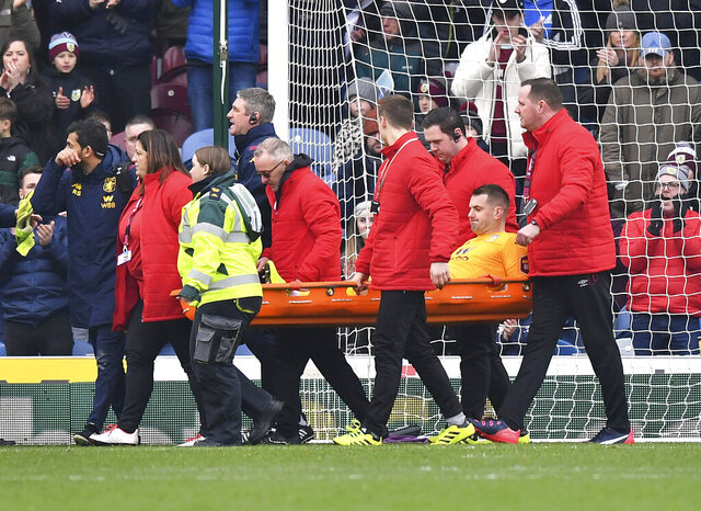 Aston Villa goalkeeper Tom Heaton, centre, is carried off the pitch on a stretcher, during the English Premier League soccer match between Burnley and Aston Villa, at Turf Moor, Burnley, England, Wednesday Jan. 1, 2020. (Anthony Devlin/PA via AP)