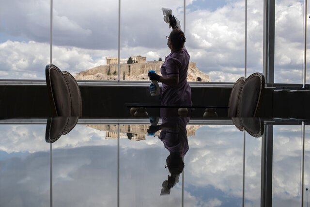 Hotel worker Mailinda Kaci cleans the windows in a restaurant area at the Acropolian Spirit Hotel in central Athens as the ancient Acropolis is seen in the background, on Monday June 1, 2020. Lockdown restrictions were lifted on non-seasonal hotels Monday as the country prepares to start its tourism season on June 15. (AP Photo/Petros Giannakouris)