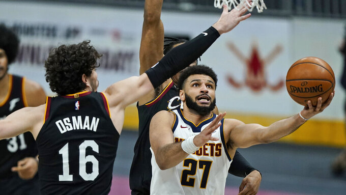 Denver Nuggets' Jamal Murray (27) drives to the basket against Cleveland Cavaliers' Cedi Osman (16) during the second half of an NBA basketball game, Friday, Feb. 19, 2021, in Cleveland. (AP Photo/Tony Dejak)