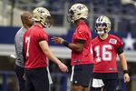 New Orleans Saints quarterback Jameis Winston (2) talks with fellow quarterback Taysom Hill (7) as quarterback Ian Book (16) looks on during NFL football practice in Arlington, Texas, Tuesday, Aug. 31, 2021. (AP Photo/LM Otero)