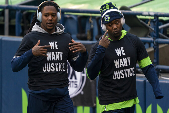 FILE - Seattle Seahawks cornerback Shaquill Griffin, left, and linebacker Shaquem Griffin are shown during warmups before an NFL football game against the Lost Angeles Rams in Seattle, in this Sunday, Dec. 27, 2020, file photo. The Griffin twins are already talking trash three months before they're on opposite sidelines for the first time in their lives. Shaquill and Shaquem Griffin were teammates at every level of football growing up in St. Petersburg. They also played together at UCF and with the Seattle Seahawks the last three years. The seemingly inseparable brothers hit free agency in March and hoped to be reunited again. But it didn't work out. (AP Photo/Stephen Brashear, File)
