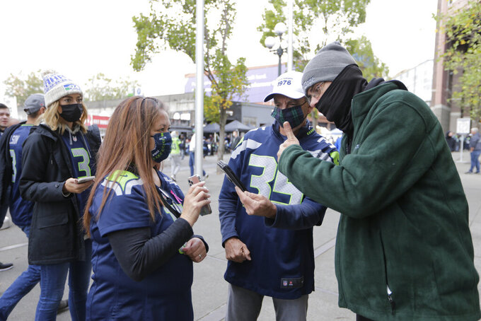 A stadium worker, right, checks for proof of vaccine against COVID-19 as fans prepare to enter Lumen Field before an NFL football game between the Seattle Seahawks and the Tennessee Titans, Sunday, Sept. 19, 2021, in Seattle. (AP Photo/John Froschauer)