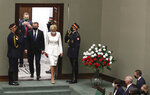 Poland's parliament guards salute as President Andrzej Duda, second left, arrives for a ceremony of his swearing in for a second term, in the company of First Lady Agata Kornhauser-Duda at the parliament, in Warsaw, Poland, on Thursday, August 6, 2020. Many of Poland's former leaders abstained from the ceremony to show disapproval for his first term policies. (AP Photo/Czarek Sokolowski)