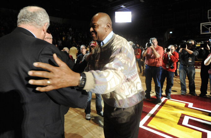 FILE - Team captain Jerry Harkness right, and other members of the 1963 Loyola men's basketball championship team meet Illinois Gov. Pat Quinn, left, during a halftime ceremony honoring the 1963 Loyola and Mississippi State teams in Chicago, in this Saturday, Dec. 15, 2012, file photo. Harkness, who led Loyola Chicago to a barrier-breaking national basketball championship and a was civil rights pioneer, has died. He was 81. The school announced Harkness passed away Tuesday morning, Aug. 24, 2021. (AP Photo/Paul Beaty, File)