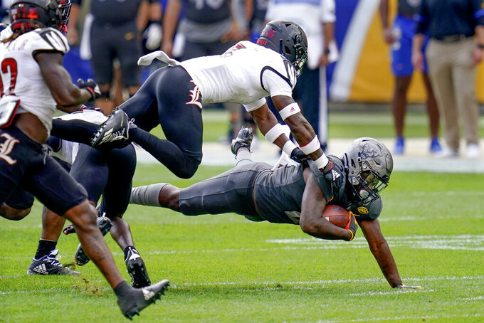 Pittsburgh running back A.J. Davis (21) dives for extra yardage as Louisville defensive back Russ Yeast (3) dives for the tackle during the first half of an NCAA college football game, Saturday, Sept. 26, 2020, in Pittsburgh. (AP Photo/Keith Srakocic)