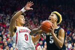 Colorado guard D'Shawn Schwartz (5) drives on Arizona guard Josh Green during the first half of an NCAA college basketball game Saturday, Jan. 18, 2020, in Tucson, Ariz. (AP Photo/Rick Scuteri)