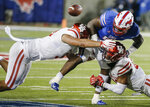 Houston linebacker Elijah Gooden, right, and defensive lineman Logan Hall, left, force SMU running back Ke'Mon Freeman (2) to fumble during the second half of an NCAA college football game Saturday, Nov. 3, 2018, in Dallas. (AP Photo/Brandon Wade)