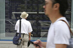 A man looks at an electronic stock board of a securities firm in Tokyo, Tuesday, July 17, 2018. Asian markets fell on Tuesday as mounting tensions over U.S. tariffs overshadowed data suggesting global growth was still on track. (AP Photo/Koji Sasahara)