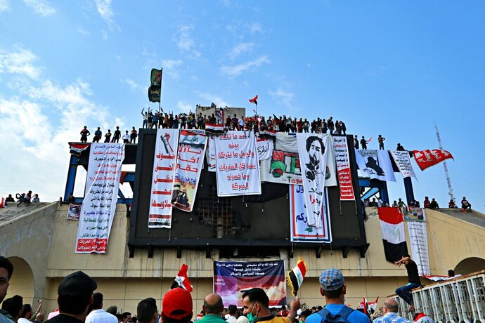 """In this Oct. 30, 2019, photo, Iraqi anti-government protesters hang their demands and slogans while standing on a building near Tahrir Square, Baghdad, Iraq. An abandoned building in central Baghdad has emerged as the epicenter of anti-government protests in Iraq, with hundreds holed up inside. The Saddam Hussein-era building known as the """"Turkish Restaurant"""" overlooks Tahrir Square, the Tigris River and the Green Zone, and protesters who took it over on Oct. 25 have sworn not to leave it. (AP Photo/Hadi Mizban)"""