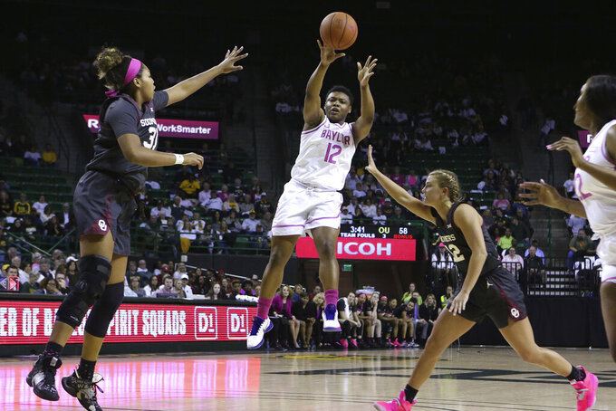 Baylor guard Moon Ursin (12) passes the ball against Oklahoma center Aspen Williston (31) and guard Gabby Gregory (12) in the second half of an NCAA college basketball game Saturday, Feb. 22, 2020, in Waco, Texas. (AP Photo/ Jerry Larson)
