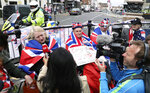 Royal fan Terry Hutt, center, waits with fellow fans along the carriage route, as TV and journalists film and interview them in Windsor, England, Wednesday, May 16, 2018. Preparations continue in Windsor ahead of the royal wedding of Britain's Prince Harry and Meghan Markle Saturday May 19, which includes a 30 minute carriage route taking the couple round the town to wave to the crowds, some of whom are already taking up positions . (AP Photo/Alastair Grant)